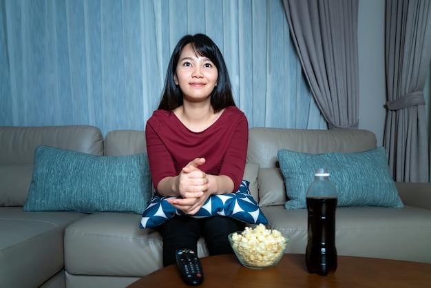 Young asian woman watching television suspense movie or news looking happy and relax and eating popcorn late night at home living room couch.