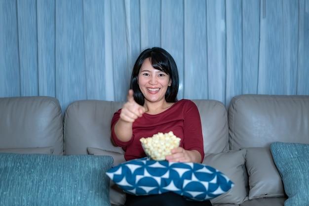 テレビのサスペンス映画やニュースを見て幸せで面白いとポップコーンを家の隔離の時間中に家のリビングルームのソファで夜遅くまで食べる若いアジア女性。