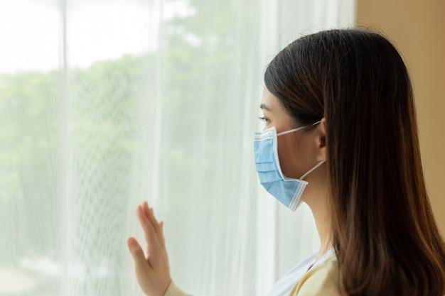 若いアジアの女性はフェイスマスクを着用します。防止covid 19、コロナウイルス、パンデミックの状況の概念。