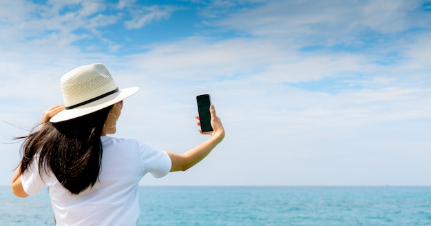 Young asian woman wear hat in casual style use smartphone taking selfie at pier. summer vacation at tropical paradise beach. happy girl travel on holiday. summer vibes.