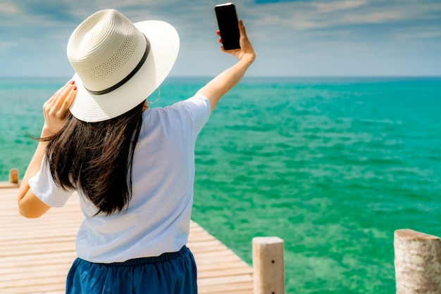Young asian woman wear straw hat in casual style use smartphone taking selfie at wooden pier. summer vacation at tropical paradise beach. happy girl travel on holiday.