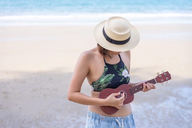 Young asian woman wear swimsuit  playing on the ukulele at beach. summer season