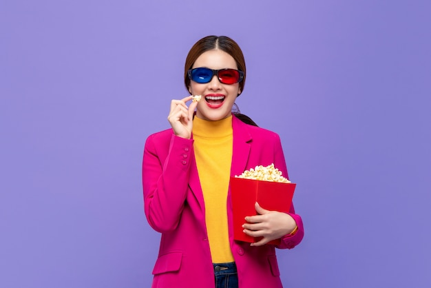 Young asian woman wearing 3d glasses enjoying eating popcorn and watching movie