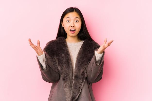 Молодая азиатская женщина в пальто, получая приятный сюрприз, взволнован и поднимая руки
