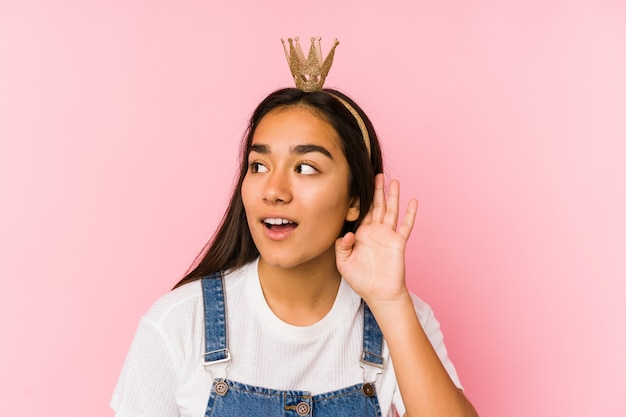 ゴシップを聞いて孤立した王冠を身に着けている若いアジアの女性