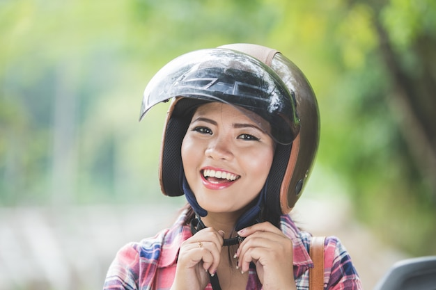 Молодая азиатская женщина нося шлем перед ездой на мотоцикле дальше