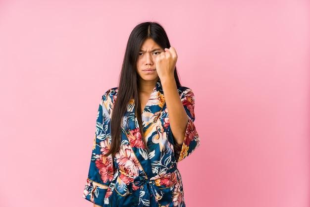 拳、積極的な表情を示す着物パジャマを着ている若いアジア女性。