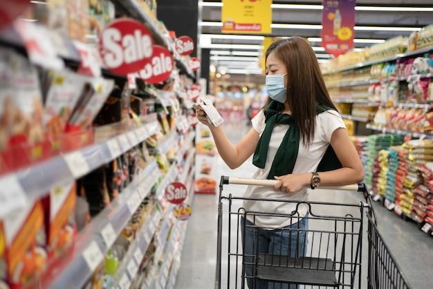 마스크를 쓰고 슈퍼마켓 선반에 제품 정보를 읽는 젊은 아시아 여자.
