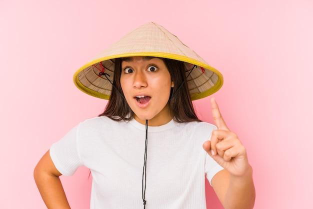 ベトナムの帽子をかぶった若いアジアの女性は、アイデア、インスピレーションの概念を持っているベトナムを身に着けている若いアジアの女性を分離しました。