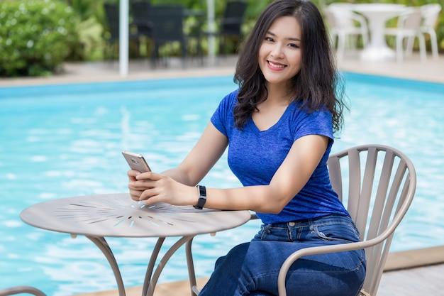 スイミングプールのそばに座っている青いトップスを着ている若いアジア女性