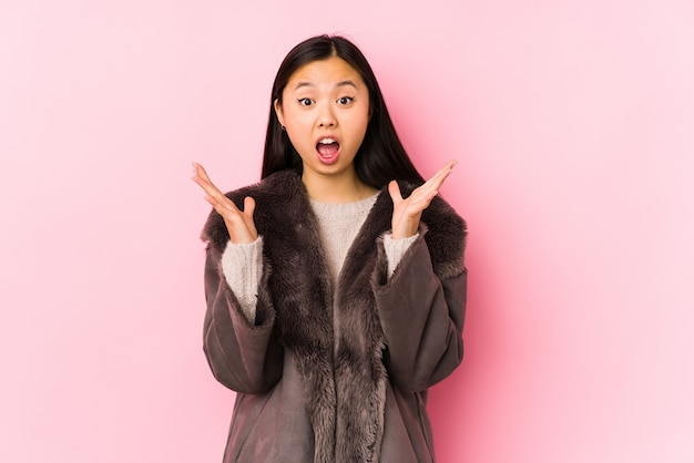 Young asian woman wearing a coat celebrating a victory or success