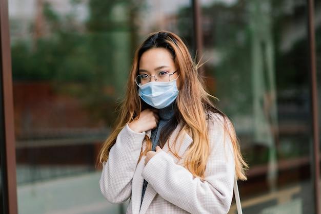 얼굴 마스크를 쓰고 젊은 아시아 여자는 국내 거리에 서 있습니다. 새로운 정상 covid-19 전염병