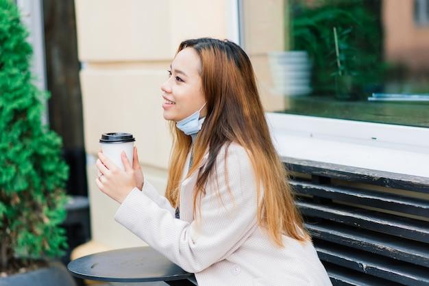 Молодая азиатская женщина в маске стоит на внутренней улице. новая нормальная эпидемия covid-19