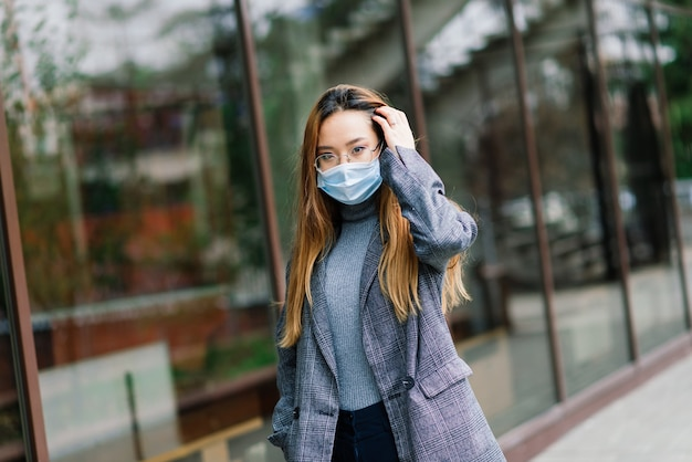 Young asian woman wearing face mask is standing at a domestic street. new normal covid-19 epidemic