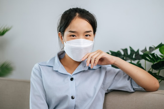 안면 마스크를 쓴 젊은 아시아 여성이 거실 소파에 앉아 집에서 코비드-19 자가 격리 기간 동안 책을 읽고 있다