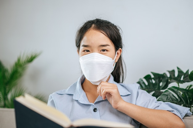 Young asian woman wearing face mask sitting on sofa in the living room, she reading book during quarantine covid-19 self isolation at home