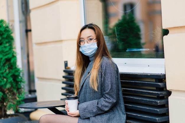 Молодая азиатская женщина в маске, стоящая на внутренней улице