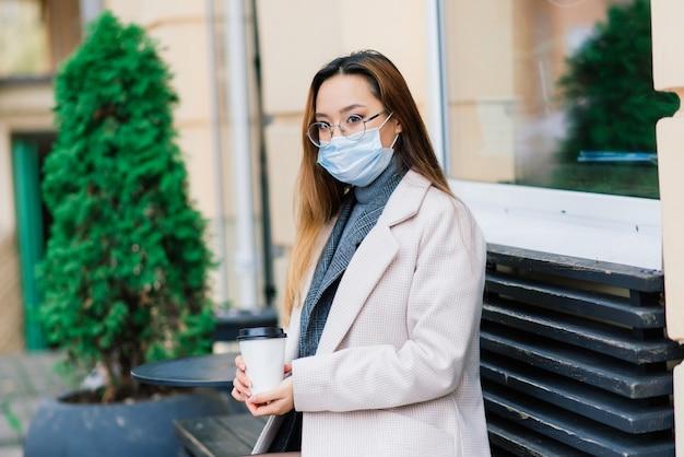 국내 거리에 얼굴 마스크 서 입고 젊은 아시아 여자