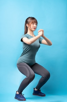 Young asian woman wearing gym suit on blue