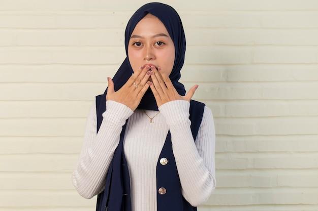 間違いのために手でショックを受けたカバー口の上にヒジャーブを着ている若いアジアの女性。秘密のコンセプト。