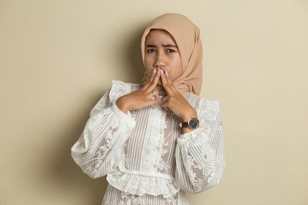 Молодая азиатская женщина в хиджабе потрясла прикрытием рта руками за ошибку. секретная концепция.