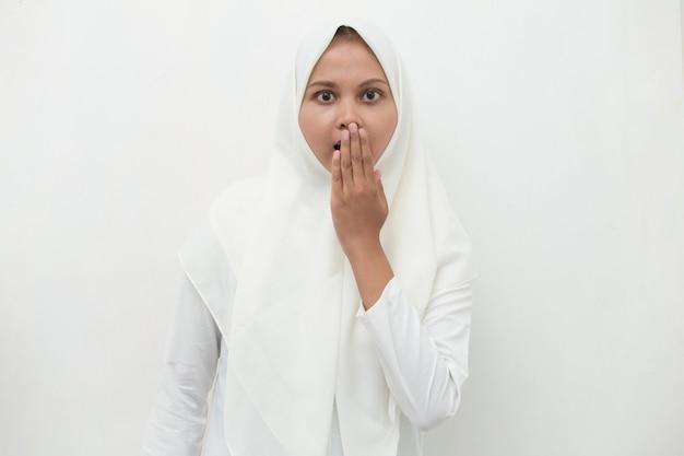 히잡을 입고 젊은 아시아 여자는 실수로 손으로 입을 덮고 충격