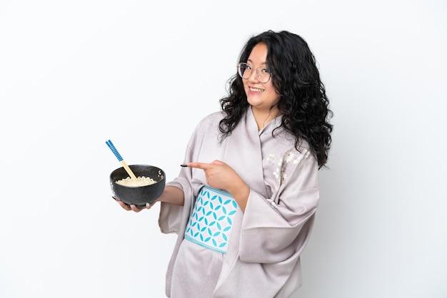 白い背景で隔離の着物を着て、箸で麺のボウルを保持しながらそれを指す若いアジアの女性