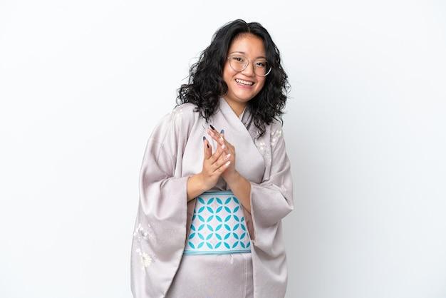 Молодая азиатская женщина в кимоно на белом фоне аплодирует после презентации на конференции