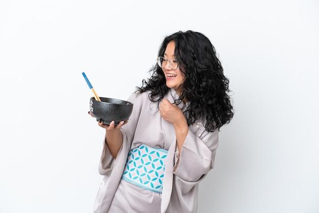Молодая азиатская женщина в кимоно на белом фоне празднует победу, держа миску лапши с палочками для еды
