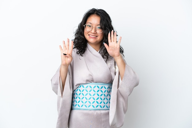 Молодая азиатская женщина в кимоно изолирована на белом фоне, считая девять пальцами