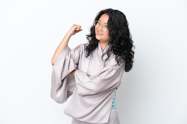 Молодая азиатская женщина в кимоно на белом фоне делает сильный жест