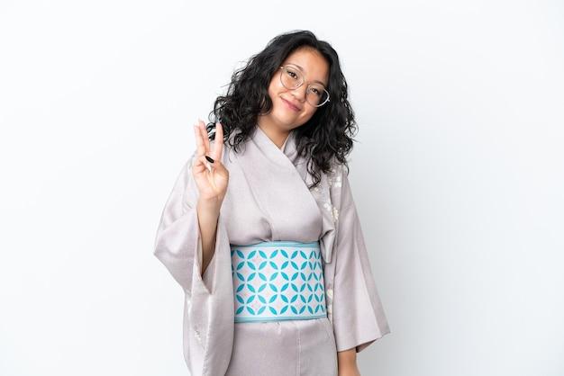 幸せな白い背景で隔離の着物を着て、指で3を数える若いアジアの女性