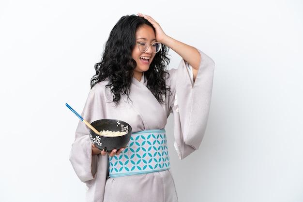 白い背景で隔離の着物を着ている若いアジアの女性は、箸で麺のボウルを保持しながら何かを実現し、解決策を意図しています