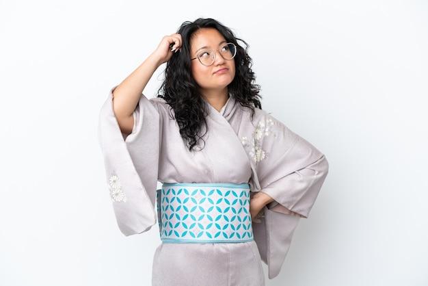 疑問と混乱した表情で白い背景に分離された着物を着ている若いアジアの女性