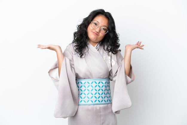 手を上げながら疑問を持っている白い背景で隔離の着物を着ている若いアジアの女性