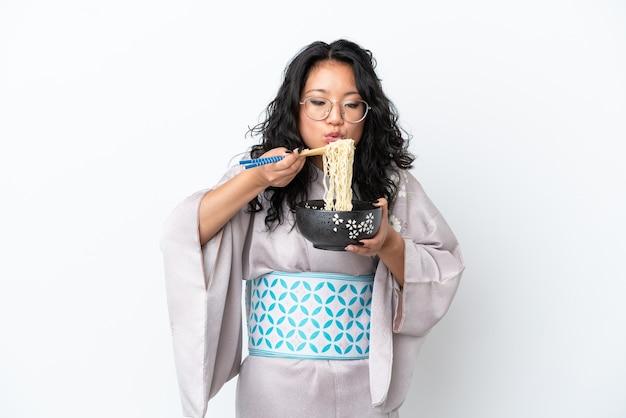Молодая азиатская женщина в кимоно на белом фоне держит миску лапши с песком для еды, дует, потому что они горячие