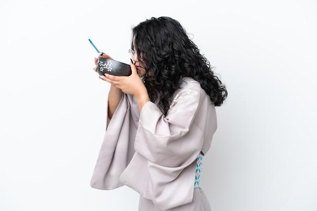 Молодая азиатская женщина в кимоно на белом фоне держит миску лапши с палочками для еды и ест ее