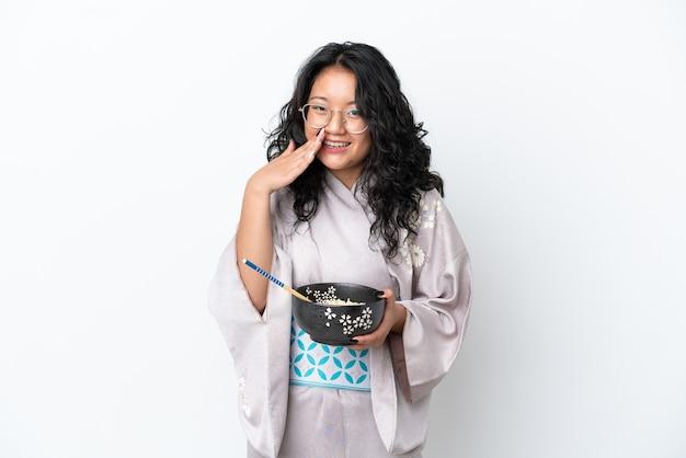 Молодая азиатская женщина в кимоно, изолированная на белом фоне, держит миску лапши с палочками для еды и удивлена