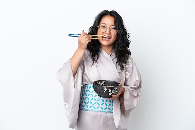 箸で麺のボウルを保持している白い背景で隔離の着物を着て若いアジアの女性