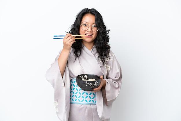 Молодая азиатская женщина в кимоно на белом фоне держит миску лапши с палочками для еды