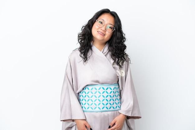 Молодая азиатская женщина в кимоно на белом фоне смеется