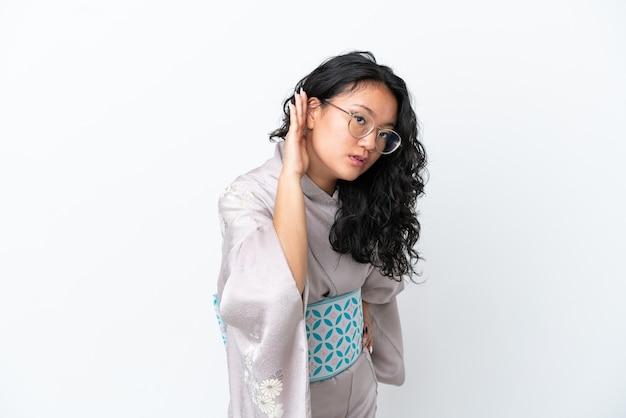 Молодая азиатская женщина в кимоно изолирована на белом фоне, слушая что-то, положив руку на ухо
