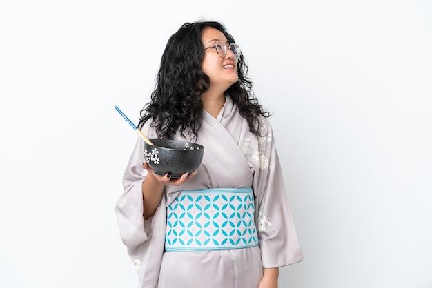 Молодая азиатская женщина в кимоно на белом фоне смотрит вверх, улыбаясь, держа миску лапши с палочками для еды