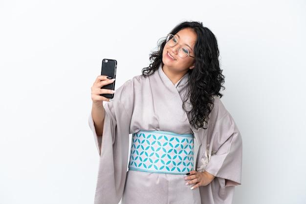 Молодая азиатская женщина в кимоно на белом фоне делает селфи