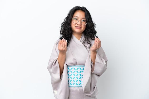 Молодая азиатская женщина в кимоно изолирована на белом фоне, делая денежный жест