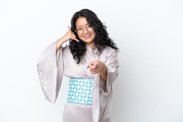 Молодая азиатская женщина в кимоно изолирована на белом фоне, делая жест телефона и указывая вперед