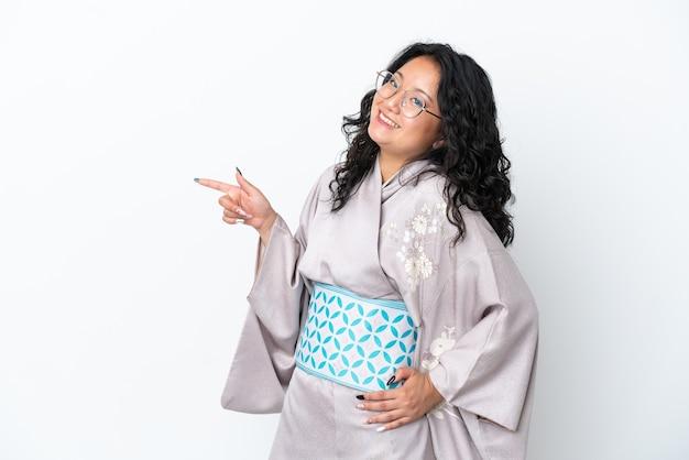 Молодая азиатская женщина в кимоно на белом фоне, указывая пальцем в сторону и представляя продукт