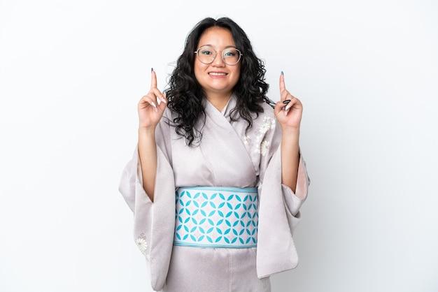 素晴らしいアイデアを指している白い背景で隔離の着物を着ている若いアジアの女性