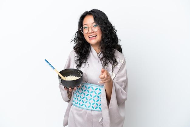 白い背景で隔離の着物を着ている若いアジアの女性は、箸で麺のボウルを保持しながら自信を持ってあなたに指を指しています