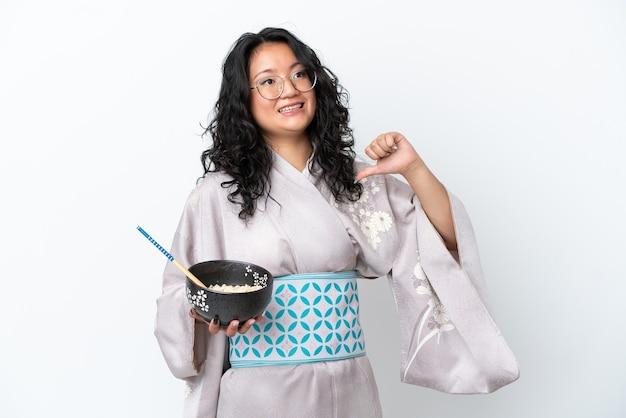 Молодая азиатская женщина в кимоно, изолированная на белом фоне, гордая и самодовольная, держа миску лапши с палочками для еды